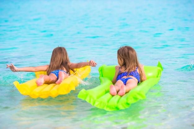 Menina adorável no colchão de ar inflável no mar