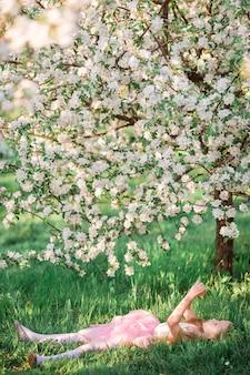Menina adorável no jardim de cerejeira desabrocham na primavera