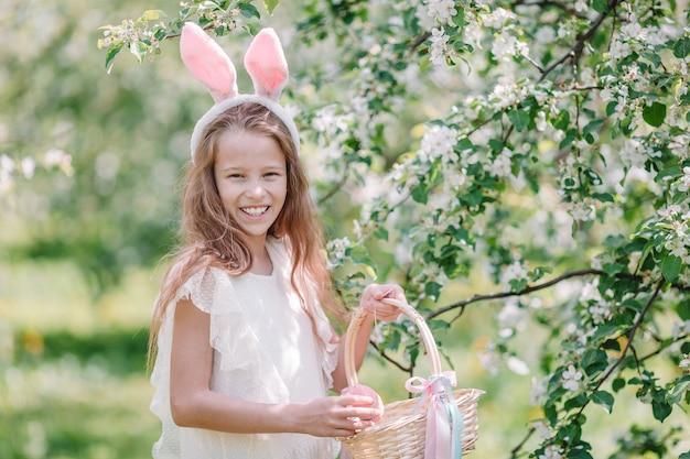 Menina adorável no jardim de maçã florescendo no lindo dia de primavera