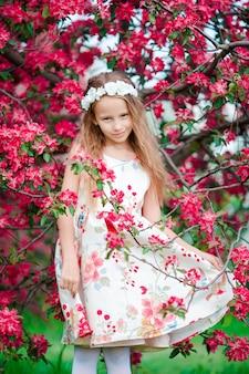 Menina adorável no jardim de macieira florescendo na primavera