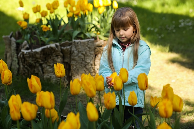 Menina adorável no jardim de tulipas florescendo