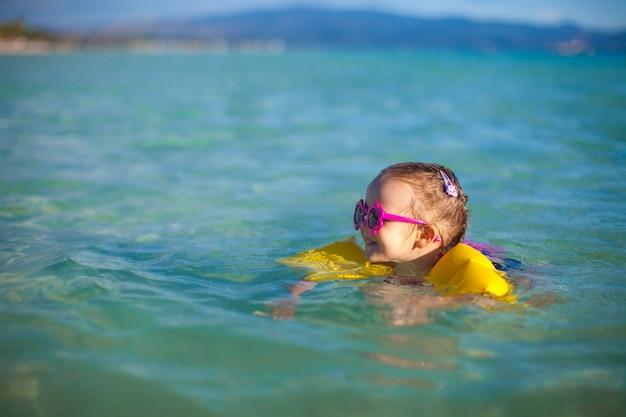 Menina adorável no mar em férias de praia tropical