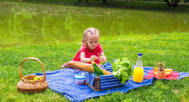 Menina adorável no piquenique ao ar livre perto do lago