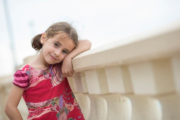Menina adorável penteada com tranças ao ar livre.