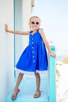 Menina adorável pequena no vestido ao ar livre em ruas velhas um mykonos.