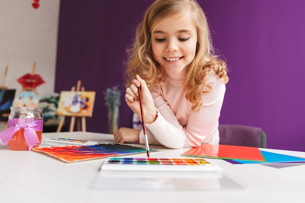 Menina adorável pintando um quadro na mesa em casa