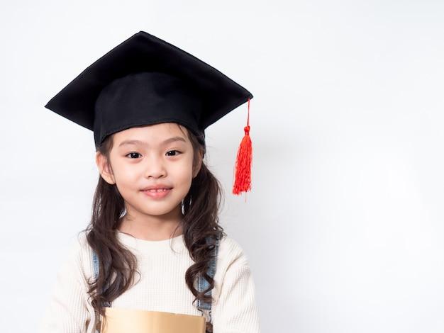 Menina adorável pré-escolar 6 anos de idade usando chapéu de formatura e segurando um livro nas mãos na parede branca.