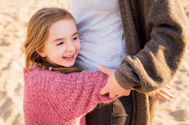 Menina adorável que abraça a mãe tiro médio
