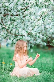 Menina adorável que aprecia o dia de mola no jardim de florescência da maçã