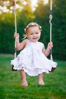 Menina adorável que aprecia um passeio do balanço em um campo de jogos em um parque