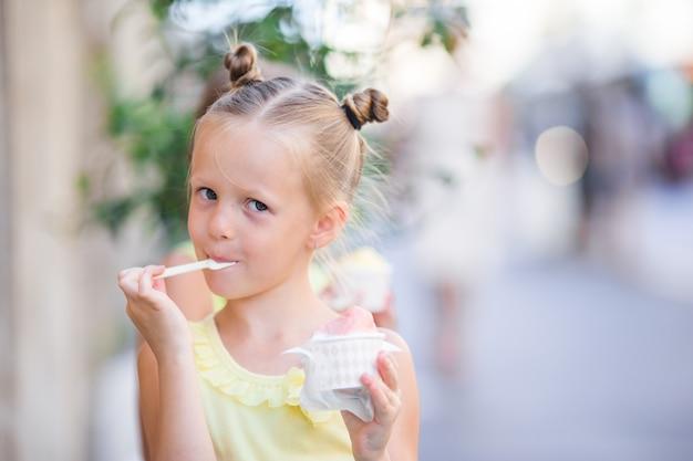 Menina adorável que come o gelado ao ar livre no verão.