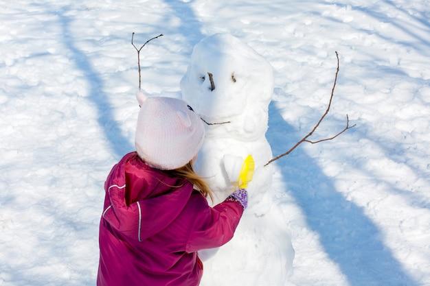 Menina adorável que constrói um boneco de neve no parque do inverno. bonita criança brincando em uma neve.