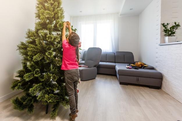 Menina adorável que decora a árvore de natal com as quinquilharias de vidro coloridas em casa