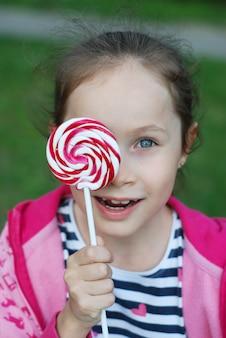 Menina adorável que guarda o pirulito do redemoinho. se divertindo.