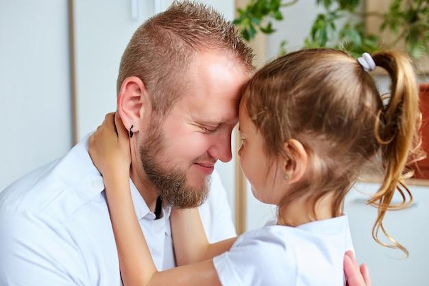 Menina adorável vestido branco, abraçando o pai amoroso