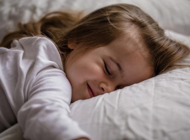 Menina adormece na cama no travesseiro branco