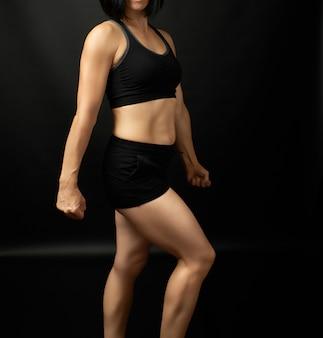 Menina adulta com uma figura de esportes em sutiã preto e calção preto
