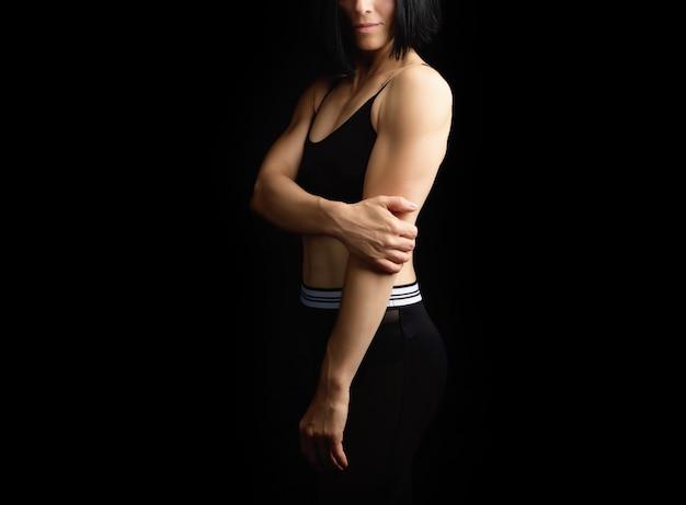Menina adulta com uma figura de esportes no sutiã preto e calção preto em pé