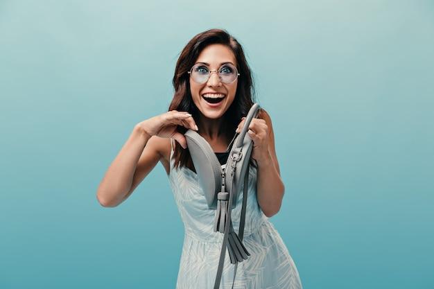 Menina adulta de olhos azuis alegre abre a pequena bolsa. mulher engraçada em sorrisos de óculos de sol redondos e poses em fundo isolado.