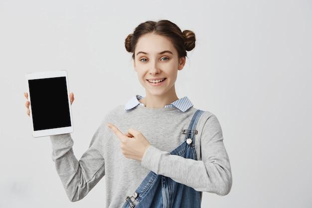 Menina adulta de sorriso com o cabelo amarrado nos bolos dobro que guardam o dispositivo moderno que aponta o dedo nele. vendedora alegre altamente recomendável nova versão do tablet na moda. marketing, vendas