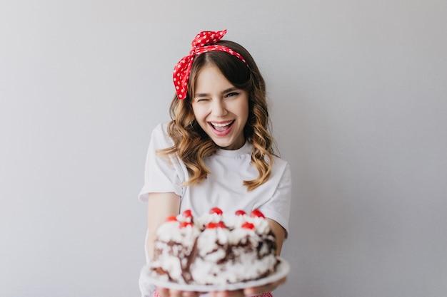 Menina afável com penteado romântico, posando com bolo de aniversário. rindo incrível senhora segurando torta de morango.