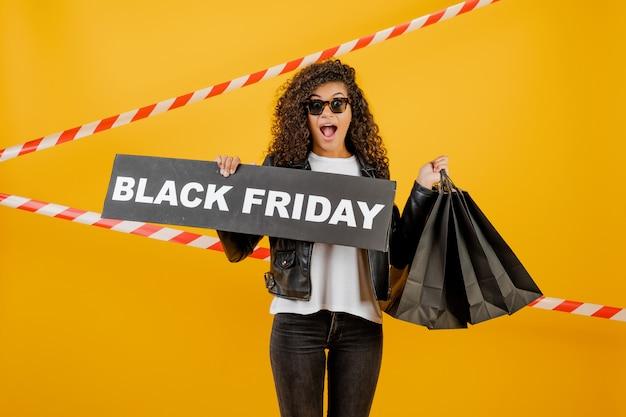 Menina africana animada com sinal de sexta-feira preta e sacolas de papel isoladas sobre o amarelo com fita de sinal
