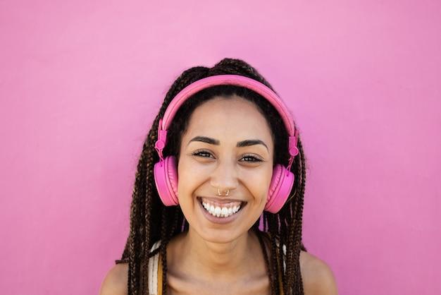 Menina africana boêmia ouve playlists de música com fones de ouvido - foco no rosto