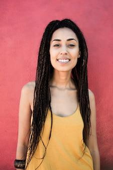 Menina africana boêmia sorrindo para a câmera ao ar livre com fundo vermelho - foco no rosto