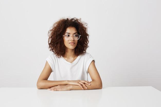 Menina africana bonita jovem sorrindo sentado à mesa sobre o espaço da cópia de parede branca.