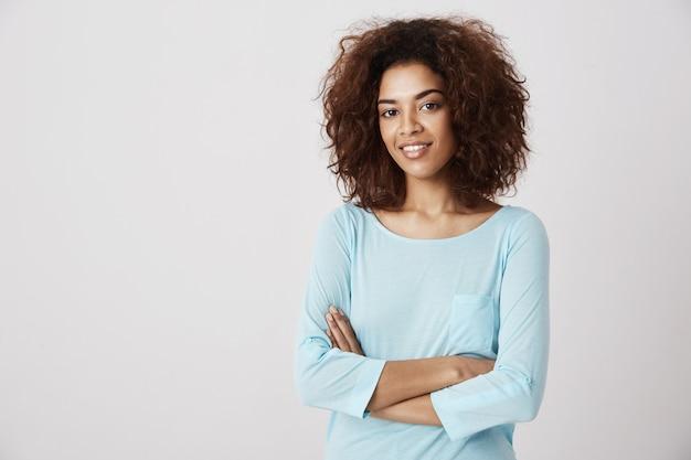 Menina africana bonita que sorri posando com os braços cruzados sobre a parede branca. copie o espaço.