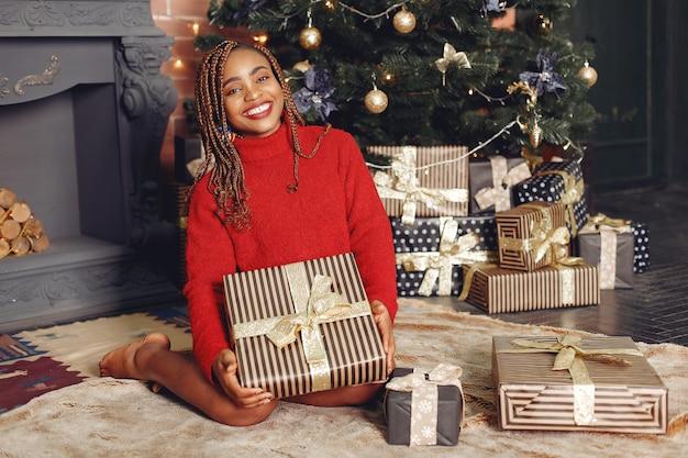 Menina africana com decorações de natal / mulher com uma camisola vermelha. conceito de ano novo.