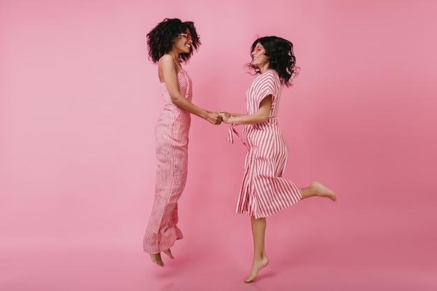 Menina africana com penteado encaracolado, pulando e de mãos dadas com um amigo. despreocupada modelo feminina em um vestido rosa arrepiante.