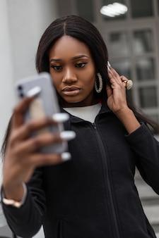 Menina africana com smartphone caminhando pela cidade