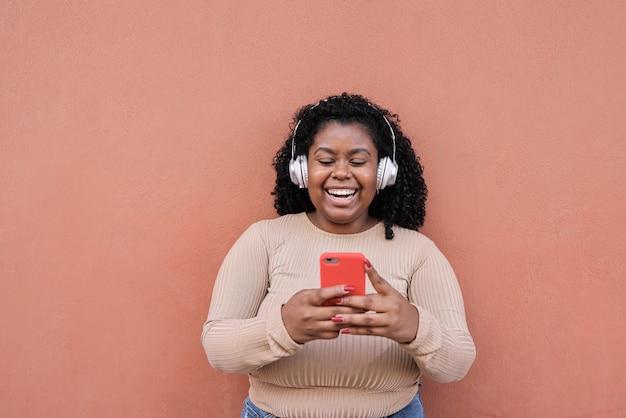 Menina africana curvilínea ouvindo música da lista de reprodução enquanto olha no celular - menina milenar se divertindo com as tendências de tecnologia - foco no rosto