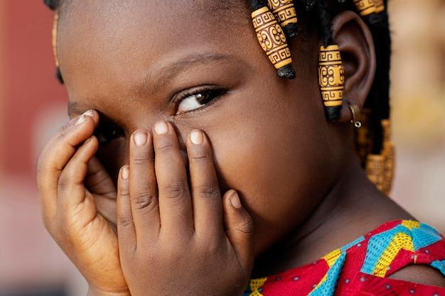 Menina africana em close cobrindo o rosto