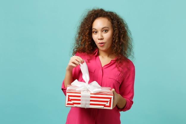 Menina africana espantada com roupas casuais segura caixa de presente listrada vermelha com fita de presente isolada no fundo da parede azul turquesa. conceito de feriado de aniversário do dia internacional da mulher. simule o espaço da cópia.