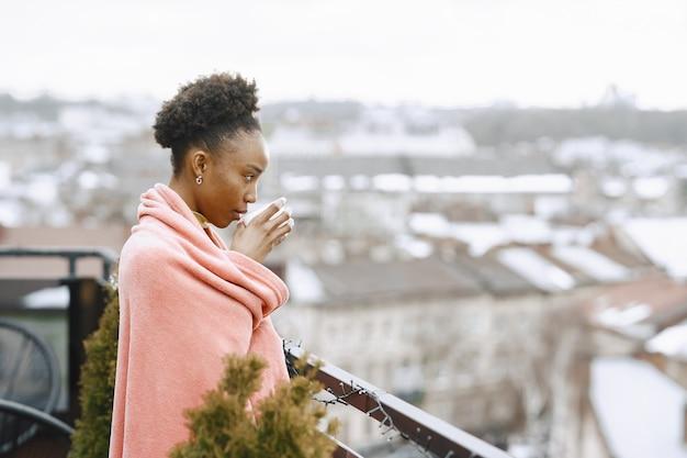 Menina africana no terraço. mulher tomando café em uma manta rosa. senhora posando para uma foto.