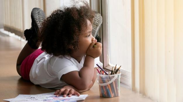 Menina africana pequena que olha através da janela.