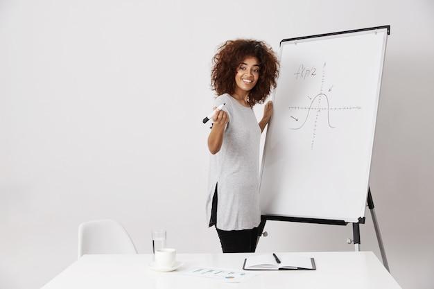 Menina africana que sorri estando perto do quadro branco do marcador sobre a parede branca.