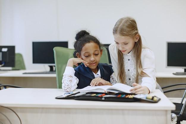 Menina africana sentada à mesa. colegiais lêem um livro durante um intervalo. crianças sentam em uma aula de ciência da computação.
