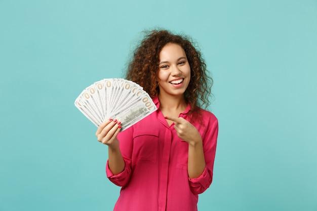 Menina africana sorridente apontando o dedo indicador no leque de dinheiro nas notas de dólar, dinheiro isolado no fundo da parede azul turquesa. emoções sinceras de pessoas, conceito de estilo de vida. simule o espaço da cópia.