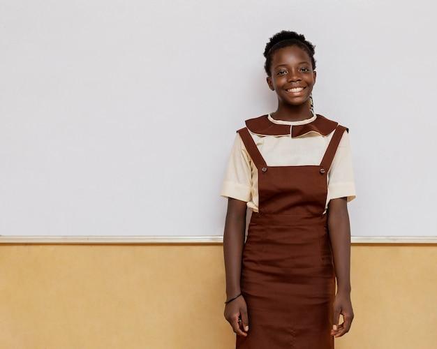 Menina africana sorridente em pé na sala de aula