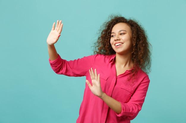 Menina africana sorridente em roupas casuais, acenando e cumprimentando com as mãos, enquanto avisa alguém isolado em um fundo azul turquesa no estúdio. conceito de estilo de vida de emoções sinceras de pessoas. simule o espaço da cópia.