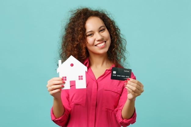 Menina africana sorridente em roupas casuais rosa segurando a casa de papel, cartão de crédito isolado no fundo da parede azul turquesa no estúdio. emoções sinceras de pessoas, conceito de estilo de vida. simule o espaço da cópia.
