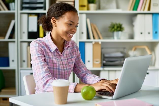Menina africana sorridente, estudando na biblioteca