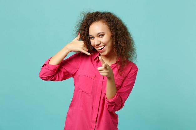 Menina africana sorridente, fazendo o gesto do telefone como diz me ligue de volta, apontando o dedo indicador na câmera isolada sobre fundo azul turquesa. emoções sinceras de pessoas, conceito de estilo de vida. simule o espaço da cópia.