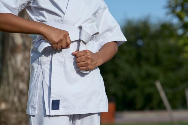 Menina afro-americana amarrando o cinto no quimono do caratê
