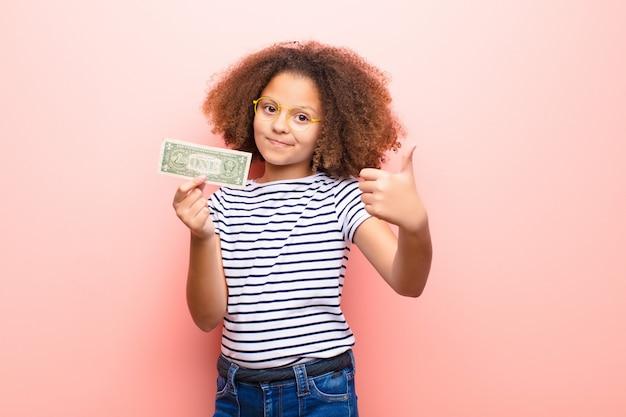 Menina afro-americana contra parede plana com notas de dólar