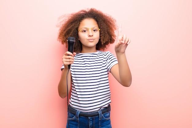 Menina afro-americana contra parede plana com um microfone