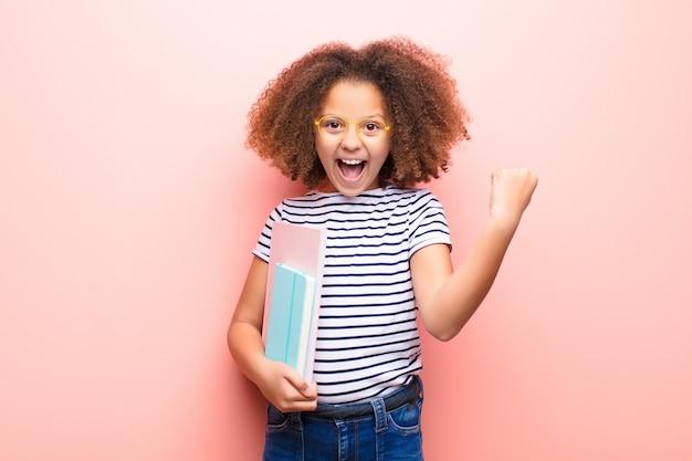 Menina afro-americana contra parede plana, segurando um livro